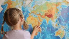 Little girl showing Africa on a geographical map - stock footage