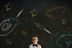 Stock Photo of thinking boy business man with chalk universe planet solar system on blackboa