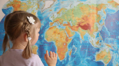 Stock Video Footage of Little girl looking for Europa (Eurasia) on a geographical map