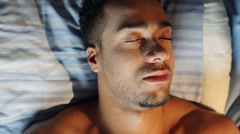 Young man waking up in bed Stock Footage