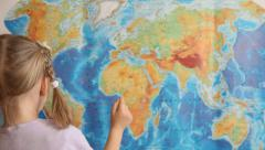 Little girl looking for South America on a geographical map - stock footage
