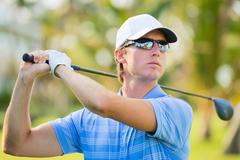 Young man swinging golf club Stock Photos