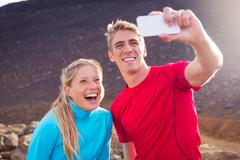 young attractive athletic couple taking photo of themselves with smart phone, - stock photo