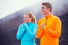 young attractive athletic couple, wearing sporty cloths on trail - stock photo