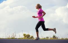 Athletic woman jogging outside, training outdoors. running on road at sunset Stock Photos