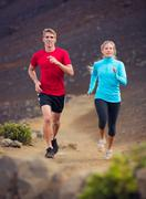fitness sport couple running jogging outside on trail - stock photo