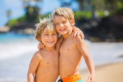 Happy young kids playing at the beach on summer vacation Stock Photos
