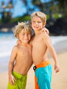 Stock Photo of happy young kids playing at the beach on summer vacation