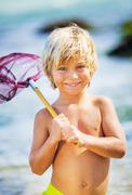 happy young boy having fun at the beach, playing with fishing net, tropical v - stock photo