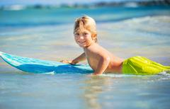 Happy young boy in the ocean on surfboard Stock Photos