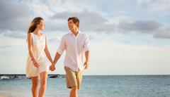 romantic happy couple walking on beach at sunset. smiling holding hands. man  - stock photo