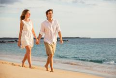 Romantic happy couple walking on beach at sunset. smiling holding around each Stock Photos