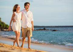 romantic happy couple walking on beach at sunset. smiling holding around each - stock photo