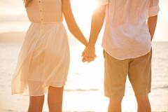 Couple holding hands at sunset on beach. romantic young couple in love Stock Photos