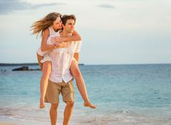 Romantic happy couple on the beach at sunset, man and woman in love Stock Photos