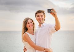 Happy romantic couple on the beach taking photo of themselves with smart phon Stock Photos