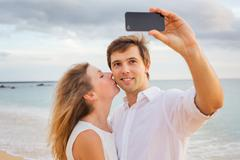 happy romantic couple on the beach taking photo of themselves with smart phon - stock photo