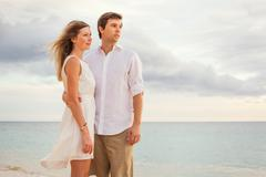 happy romantic couple on the beach at sunset embracing each other. man and wo - stock photo