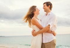 Happy romantic couple on the beach at sunset embracing each other. man and wo Stock Photos