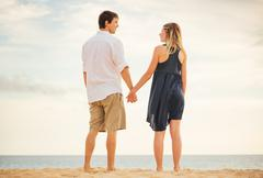 Romantic happy couple on beach at sunset. smiling holding hands. man and woma Stock Photos