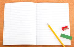 an opened notebook, pencil and stationery on a wooden table. - stock photo