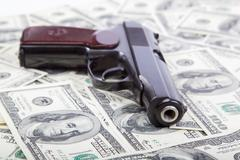 money and weapons. gun against the dollar bills. - stock photo