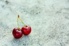 Two cherries on gray background Stock Photos