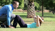 Stock Video Footage of Young woman doing crunches in park with help of personal trainer HD