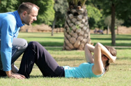 Stock Video Footage of Young woman doing crunches in park with help of personal trainer NTSC