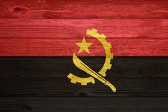 Angola flag painted on old wood plank background. Stock Photos