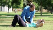 Stock Video Footage of Young woman doing crunches in park with a personal trainer HD
