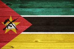 Mozambique flag painted on old wood plank background. Stock Photos