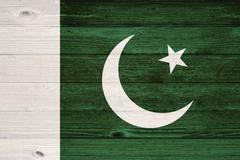 pakistan flag painted on old wood plank background. - stock photo