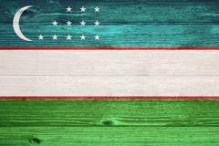 uzbekistan flag painted on old wood plank background. - stock photo