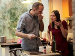 Young couple preparing and tasting a tasteless salad in the kitchen NTSC Stock Footage