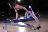 Stock Photo of Fitness Woman Working Out at the Gym with Bench and Dumbbell