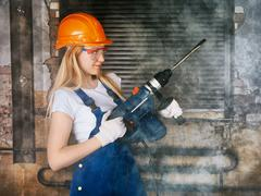 Beautiful woman with heavy drill Stock Photos