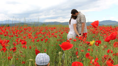 Couple of romantic parents in blossom poppies field, child go closer to parents - stock footage