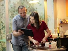 Young woman preparing food and man showing her something on tablet in kitch NTSC Stock Footage