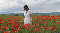 Young woman walk in blossom red poppies field, pick a flower arrange to ear - stock footage