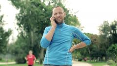 Stock Video Footage of Young jogger receiving phone call on cellphone in the park HD