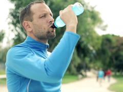 Young jogger drinking isotonic drink in the park NTSC Stock Footage