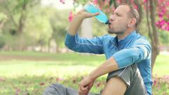 Young sportsman drinking isotonic drink, resting on grass in the park HD Stock Footage