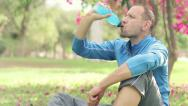 Stock Video Footage of Young sportsman drinking isotonic drink, resting on grass in the park HD