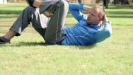 Stock Video Footage of Young sportsman doing crunches on the grasss in a park HD