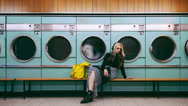Stock Video Footage of Woman waiting for laundry at launderette cinemagraph seamless loop