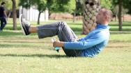 Stock Video Footage of Young man doing exercise abdominal muscles on a grass in the park HD