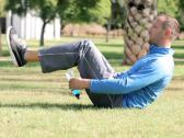 Stock Video Footage of Young man doing exercise abdominal muscles on a grass in the park NTSC