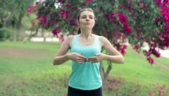 Young woman doing breathing exercises in the park HD Stock Footage