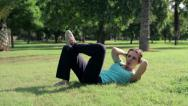 Stock Video Footage of Young sportswoman doing crunches(sit-ups) lying on grass in the park HD